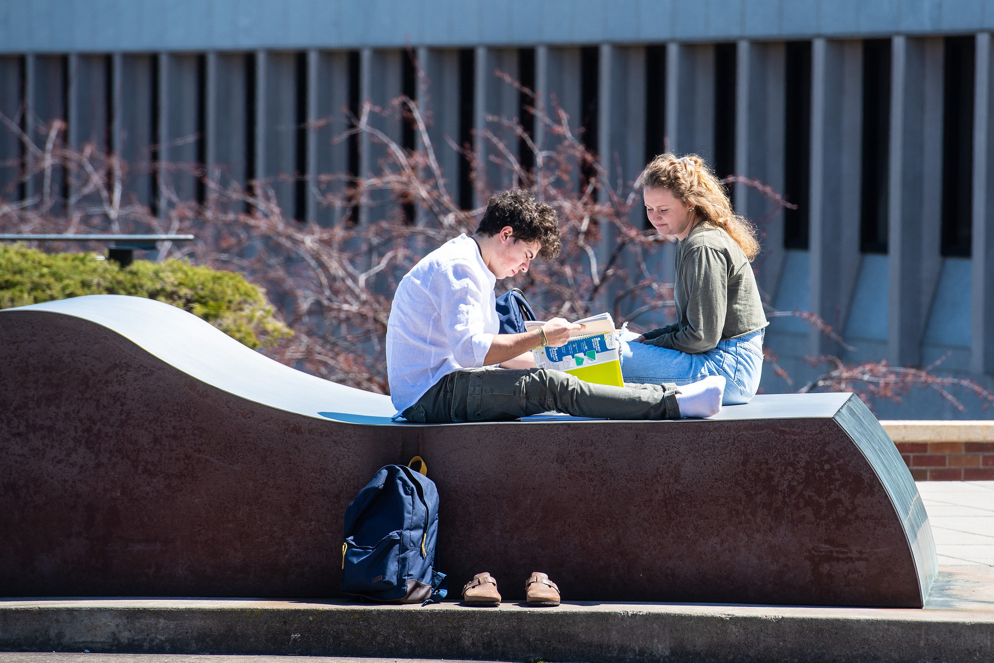 Two students studying while sitting on a flat sculpture