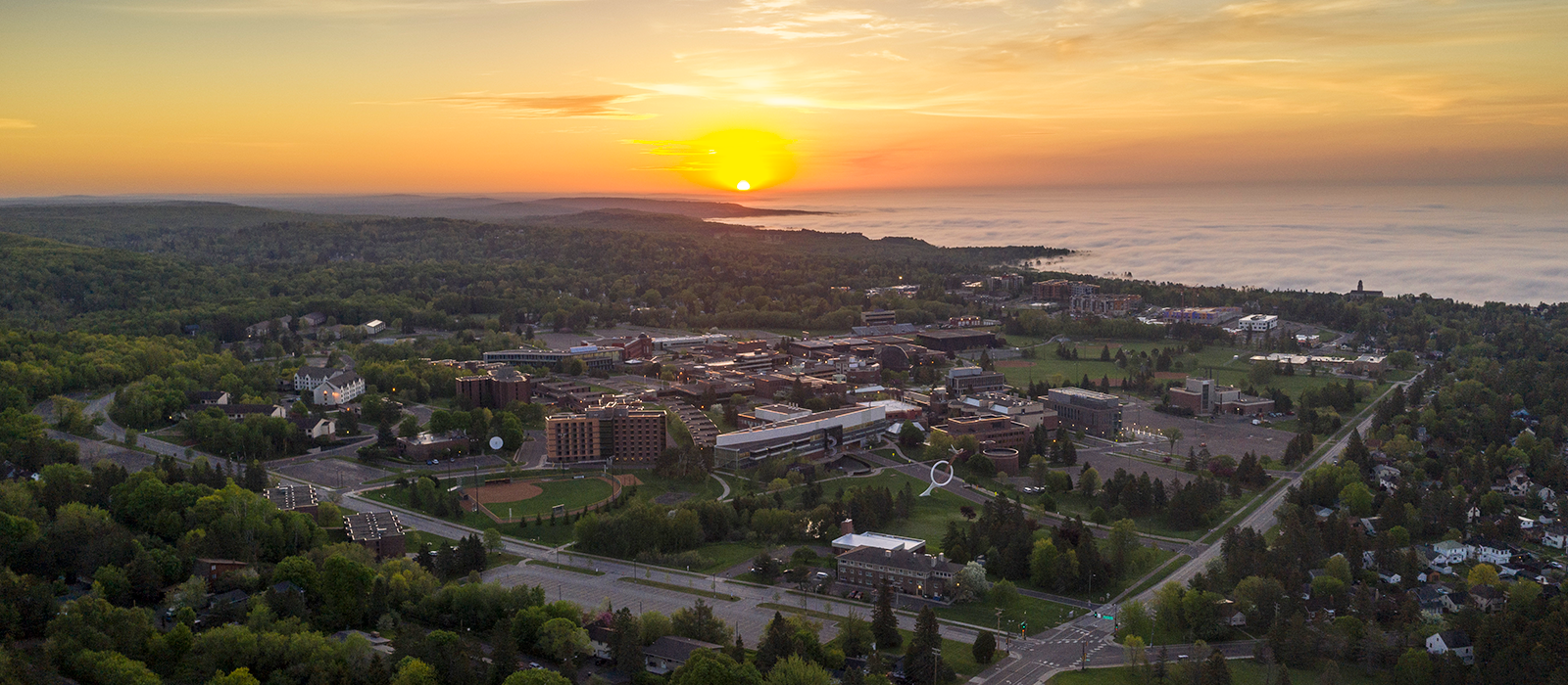 Sunset aerial shot of UMD campus and Lake Superior